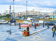 The chestnut cart. ISTANBUL, TURKEY - JANUARY 13, 2015: The roasted chestnut cart on Rustem Pasha Square with Galata Bridge on the background, on January 13 in Royalty Free Stock Image