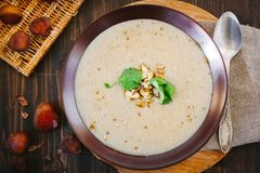 Chestnut cream soup. On brown plate with vegetables stock photography