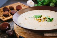 Chestnut cream soup. On brown plate with vegetables royalty free stock photos