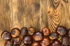 Chestnut are located on a wooden table top view. top copy space. Many chestnut fruits are located on a wooden table top view. top copy space stock photos