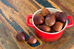 Chestnut in red bowl on wooden table. Selective focus Stock Photography