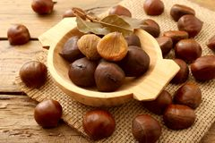 Chestnut on rustic wooden table. Chestnut raw and cooked on rustic wooden table stock photography