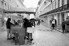 Chestnut Seller, Lisbon. Typical street chestnut seller and customers on a rainy Rua Augusta, Lisbon. Image taken at 17:50 pm 2nd November 2012 Stock Image