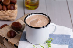 Chestnut soup in white enamel mug with roasted chestnuts Royalty Free Stock Image