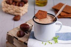 Chestnut soup in white enamel mug with roasted chestnuts Stock Photos
