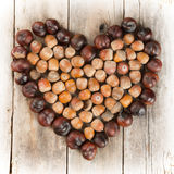 Chestnuts and acorns forming, a heart on a wooden background Royalty Free Stock Photos