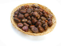Chestnuts in basket. A basket full of chestnuts on a white background.  Species:  Castanea Royalty Free Stock Photos