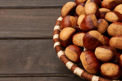 Chestnuts in a basket. Chestnuts in a big basket with wooden planks on the left Royalty Free Stock Photo