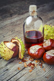 Chestnuts and bottle with tincture on wooden table Stock Photo