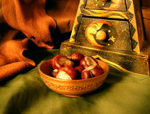 Chestnuts in a bowl. Heap of chestnuts on a wooden plate Royalty Free Stock Photos