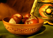 Chestnuts in a bowl. Heap of chestnuts on a wooden plate Stock Photography