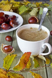 Chestnuts and coffee. Chestnuts, autumn leaves and coffee on the table Stock Photo