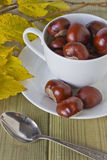 Chestnuts in a cup. And autumn leaves on the table Stock Images