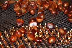 Chestnuts with fire flames, close up Royalty Free Stock Photo