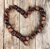 Chestnuts forming a heart on a wooden background Stock Image