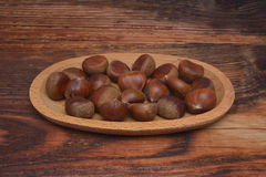 Chestnuts isolated on wooden background. Brown Royalty Free Stock Image