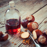 Chestnuts, knife and bottle with tincture on wooden table, herba Royalty Free Stock Photography