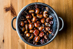 Chestnuts in metal pasta strainer to drain the water. Chestnuts in white bowl on wooden surface. organic food concept Royalty Free Stock Photos