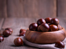 Chestnuts on the old wooden table Stock Photos