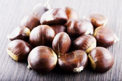 Chestnuts over wooden table Royalty Free Stock Images
