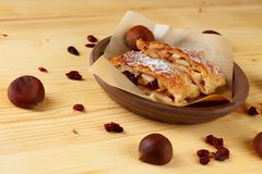 Chestnuts and raisins around apple strudel Royalty Free Stock Photos