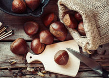 Chestnuts ready to roasting and frying pan on rustic kitchen tab Royalty Free Stock Photo