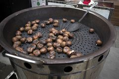Chestnuts roasted in a large pan for sale on the street. The chestnuts roasted in a large pan for sale on the street stock photography