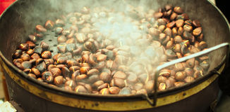 Seasonal food viewing,seasonal food picture,seasonal food image,Chestnuts,roasted,pot,food. Large pot containing roasted chestnuts steaming. seasonal food Royalty Free Stock Photography