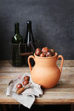 Chestnuts in a rustic clay roaster with two empty bottles in a wire basket on background Royalty Free Stock Photography