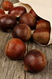 Chestnuts spilling on rustic wood background Stock Photos