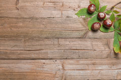 Chestnuts on a table. Chestnuts on a brown wooden table with some leaves royalty free stock image