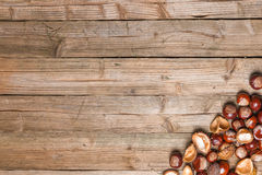 Chestnuts on a table. Chestnuts on a brown wooden table with some leaves stock image
