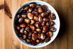 Chestnuts in white bowl on wooden surface. Organic food concept Stock Photography