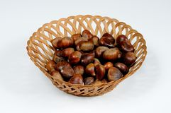 Chestnuts in wicker basket. Chestnuts in a wicker basket against a white background Stock Image
