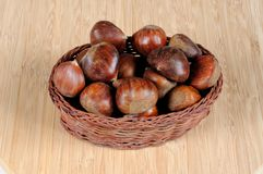 Chestnuts in wicker basket. Whole raw chestnuts in shells in a wicker basket against a wooden background Royalty Free Stock Images