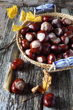 Chestnuts in  wicker basket and autumn leaves. On old wooden background Stock Image
