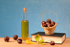 Chestnuts in wicker baskets, books and oil Stock Photo
