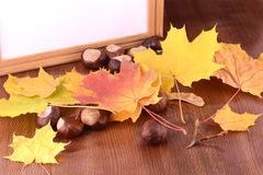 Chestnuts on wooden background and blank paper card Royalty Free Stock Photo