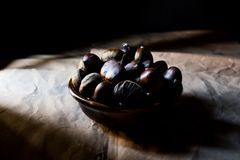 Chestnuts in wooden basket. Dark Moody. Photography Stock Image