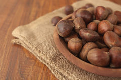 Chestnuts in a wooden bowl on a sackcloth. Stock Photo