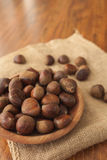 Chestnuts in a wooden bowl on a sackcloth. Royalty Free Stock Photo