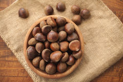 Chestnuts in a wooden bowl on a sackcloth. Royalty Free Stock Image
