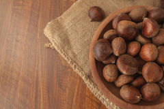 Chestnuts in a wooden bowl on a sackcloth. Stock Images