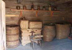 Chests, barrels and a shelf with dishes in the ancient peasant hut. Pirogovo, Ukraine Stock Image