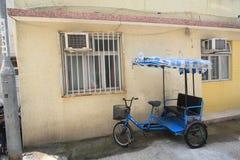 Land, vehicle, mode, of, transport, cart, motor, house, product, rickshaw, bicycle, accessory, window, street, facade. Photo of land, vehicle, mode, of stock image