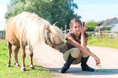 Cheval curieux obéissant de poney de Shetland avec son gir adolescent d'ami Photo libre de droits