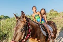 Cheval d'équitation de deux petites filles pendant l'été en Ada Bojana, Monte Photos stock