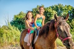 Cheval d'équitation de deux petites filles pendant l'été en Ada Bojana, Monte Photographie stock
