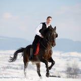 Cheval d'équitation de jeune homme extérieur en hiver Photographie stock