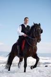 Cheval d'équitation de jeune homme extérieur en hiver Photo libre de droits